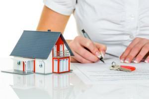 Une femme signe un contrat d'achat d'une maison avec un agent immobilier .