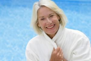 senior en peignoir devant une piscine